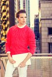 Young American man working in New York. Young man wearing red knit sweater, white pants, hold laptop computer, standing by railing facing street, confidently Royalty Free Stock Images