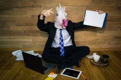 Unicorn dressing a suit and tie and drinking coffee. Young man wearing rubber mask sits on the floor against a wall and drinking coffee. Unicorn dressing a suit Stock Photo