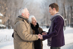 Young man wearing a scarf greets an elderly couple. Young men wearing a scarf greets an elderly couple in the park in winter Royalty Free Stock Photography