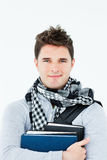 Young man wearing a scarf and holding books Stock Photo