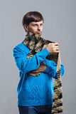 Young man wearing scarf and sweater. Young man in a sweater wraps a scarf around the neck Royalty Free Stock Images
