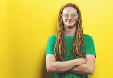 Young man wearing shutter shades sunglasses. On a yellow background Royalty Free Stock Image