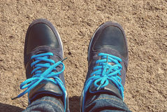 Young man wearing sport shoes with blue shoelace and jeans. Close up image. Instagram filter stock photos