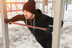 Young man wearing sportswear exercising outdoors. Young man wearing black sportswear exercising outdoors. Male adult doing push up exercise. Winter fitness Stock Images