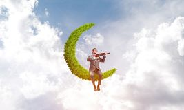 Handsome violinist on moon in blue sky play his melody Stock Images