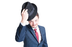 Young man wearing suit putting on elegant hat Stock Photos