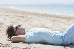 Young man wearing sunglasses lying on tne sand beach Stock Photography