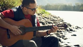 Young man wearing sunglasses plays on a guitar sitting by mountain river on sunny day in slow motion.  stock footage