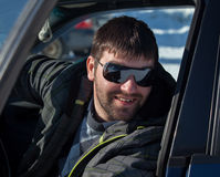 A young man wearing sunglasses in a private car Stock Photo