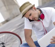 Young man relaxing on the floor and listening music. Young man wearing sunglasses relaxing on the floor and listening music Stock Photography