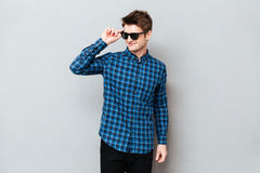 Young man wearing sunglasses standing over grey wall. Picture of young man wearing sunglasses standing over grey wall and looking aside royalty free stock image