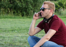 Young man wearing sunglasses talking on the phone Stock Images