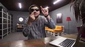Young man wearing sunglasses talks at camera and showing signs with his fingers. Attractive white bearded funny guy put on stylish sunglasses and grey checkered stock video footage