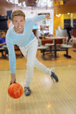 Young man wearing sweater throws ball in bowling. Young smiling man wearing blue sweater throws ball in bowling; shallow depth of field Royalty Free Stock Image