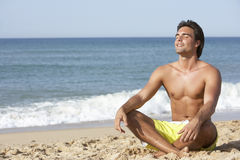 Young Man Wearing Swimming Costume Sitting On Beach Stock Photo