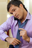 Young man wearing tie, using mobile phone Royalty Free Stock Images