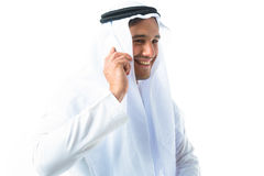 Young Man Wearing Traditional Arabic Clothing. Studio shot of young man wearing traditional arabic clothing, talking on phone Stock Photo