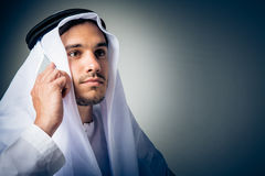 Young Man Wearing Traditional Arabic Clothing. Studio shot of young man wearing traditional arabic clothing, talking on the phone Stock Photo