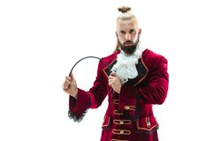 The young man wearing a traditional medieval costume of marquis. Posing at studio with whip. Fantasy, Antique, Renaissance concept royalty free stock image