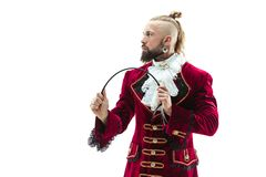 The young man wearing a traditional medieval costume of marquis. Posing at studio with whip. Fantasy, Antique, Renaissance concept royalty free stock images
