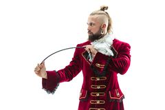 The young man wearing a traditional medieval costume of marquis. Posing at studio with whip. Fantasy, Antique, Renaissance concept stock images