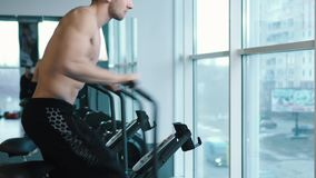 Young man wearing training hardly on cycling machine stock footage