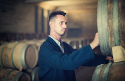 Young man wearing uniform standing and labeling woods. In winery cellar Royalty Free Stock Image