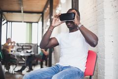 Young man wearing virtual reality glasses in modern interior design coworking studio. Smartphone using with VR goggles Stock Images