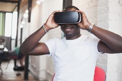 Young man wearing virtual reality glasses in modern interior design coworking studio. Smartphone using with VR goggles Stock Photo
