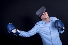 Young man wearing virtual reality goggles and boxing gloves. Young asian man wearing virtual reality goggles with black background studio in fighting pose royalty free stock photography