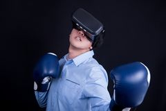 Young man wearing virtual reality goggles and boxing gloves. Young asian man wearing virtual reality goggles with black background studio in fighting pose stock image