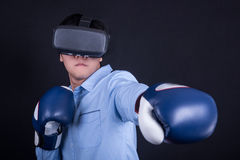 Young man wearing virtual reality goggles and boxing gloves. Young asian man wearing virtual reality goggles with black background studio in fighting pose royalty free stock image