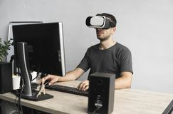 Young man wearing virtual reality goggles headset, vr box and sitting in the office against computer monitor. Connection royalty free stock images