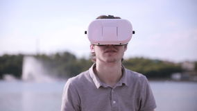 Young Man wearing virtual reality goggles outdoor. stock video