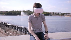 Young Man wearing virtual reality goggles outdoor. stock footage