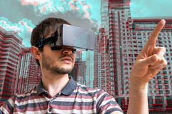 Young man is wearing virtual reality headset. 3D simulation of city Stock Photos
