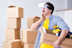 The young man wearing vr glasses moving in new apartment. Young man wearing VR glasses moving in new apartment Royalty Free Stock Images