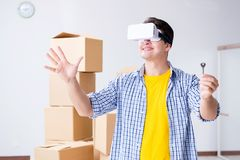 The young man wearing vr glasses moving in new apartment. Young man wearing VR glasses moving in new apartment Stock Images
