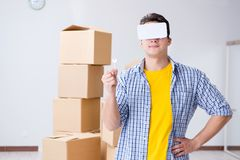 The young man wearing vr glasses moving in new apartment. Young man wearing VR glasses moving in new apartment Stock Photo