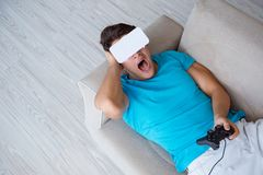 The young man wearing vr glasses relaxing on couch sofa. Young man wearing VR glasses relaxing on couch sofa Stock Photos