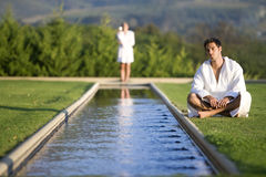 Young man wearing white bath robe, sitting outdoors by pool, woman standing in background Royalty Free Stock Photos