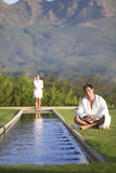 Young man wearing white bath robe, sitting outdoors by pool, woman standing in background Royalty Free Stock Photography