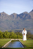 Young man wearing white bath robe, standing outdoors by pool Royalty Free Stock Image