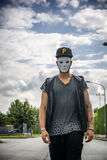 Young man wearing white creepy mask outdoor in city street Royalty Free Stock Photography