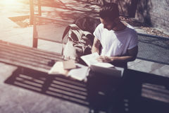 Young man wearing white tshirt sitting city park and reading book. Studying at the University, preparation for exams Stock Images