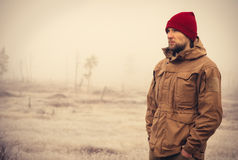 Young Man wearing winter hat clothing outdoor. With foggy nature on background Travel Lifestyle and melancholy emotions concept film effects colors Royalty Free Stock Photo
