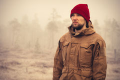 Young Man wearing winter hat clothing outdoor. With foggy nature on background Travel Lifestyle and melancholy emotions concept film effects colors Royalty Free Stock Image