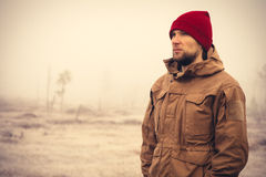 Young Man wearing winter hat clothing outdoor. With foggy nature on background Travel Lifestyle and melancholy emotions concept film effects colors Royalty Free Stock Photography