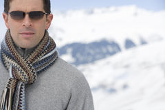 Young man wearing woolen scarf and sunglasses in snow, close-up Stock Images