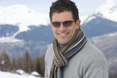 Young man wearing woolen scarf and sunglasses in snow, smiling, portrait, mountain range in background Royalty Free Stock Images